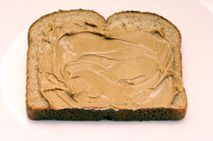 Peanut butter on bread. Peanut butter on whole grain wheat bread sitting on plate Stock Photos