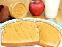 Peanut butter on bread. Creamy peanut butter on whole wheat bread on a plate Royalty Free Stock Photography