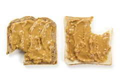Peanut butter bread with bites. Photo of two slices of white and whole wheat bread covered in peanut butter, isolated on white, with bites Royalty Free Stock Images