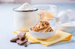 Peanut butter, chocolate chunks, eggs, sugar and cup of flour. Ingredients for baking. Selective focus Stock Photos