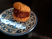 Peanut butter chocolate sandwich cookie on blue and white plate. Two vegan peanut butter cookies sandwiched together with a chocolate filling and served on a Stock Image