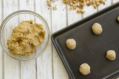 Peanut butter cookie dough on baking sheet. Raw peanut butter cookie dough in balls on baking sheet and in bowl with fresh peanuts royalty free stock photography
