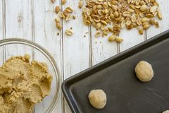 Peanut butter cookie dough balls on baking sheet. Raw peanut butter cookie dough in balls on baking sheet and in bowl with fresh peanuts royalty free stock photography