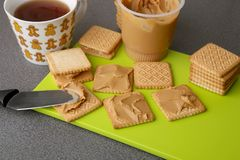 Peanut butter on cookies. Cookies with peanut butter on bright green board royalty free stock image