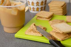Peanut butter on cookies. Cookies with peanut butter on bright green board stock photo