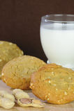 Peanut Butter Cookies with Glass of Milk. Peanut butter cookies with a glass of milk and monkey nuts on a dark brown background with a shallow DOF Royalty Free Stock Photography