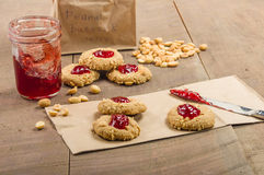Peanut butter cookies with jelly. Peanut butter cookies with strawberry jam on wooden table royalty free stock photos