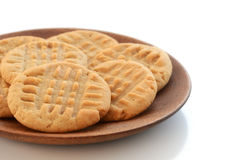 Peanut butter cookies on white background. Fresh baked peanut butter cookies on wooden plate shot in natural light with shallow depth of field.  Room for text Stock Image