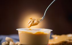 Peanut butter. Creamy smooth peanut butter in a jar on a table. Spoon of Natural nutrition. Organic food royalty free stock photography