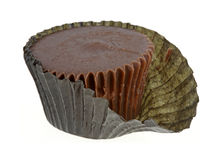 Peanut Butter Cup Partially Wrapped. A peanut butter cup with a ridged chocolate coating partially wrapped Stock Photography