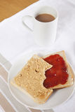 Peanut butter and jam on slices of bread with cup of coffee Royalty Free Stock Photo