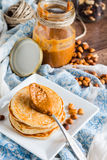 Peanut butter in a jar, eat a teaspoon and pancakes Royalty Free Stock Image