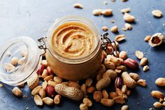 Peanut butter jar and heap of nuts on dark rustic background. Royalty Free Stock Photos