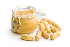 Peanut butter in jar and peanuts. Peanut butter in jar and peanuts isolated on white background stock image