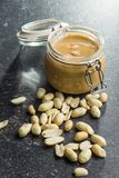 Peanut butter in jar and peanuts. Peanut butter in jar and peanuts on old kitchen table royalty free stock images
