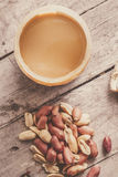 Peanut butter jar with peanuts on wooden surface Royalty Free Stock Images