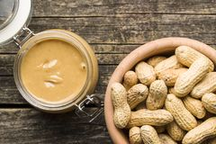 Peanut butter in jar and peanuts. Peanut butter in jar and peanuts on wooden table royalty free stock images