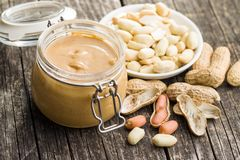 Peanut butter in jar and peanuts. Peanut butter in jar and peanuts on wooden table royalty free stock photography