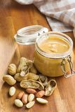Peanut butter in jar and peanuts. Peanut butter in jar and peanuts on wooden table stock image