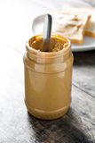 Peanut butter jar and toasts. On wooden table. Copyspace stock image