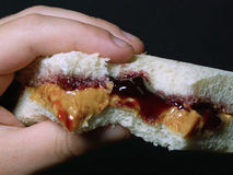 Peanut butter & jelly. Child's hand holding a peanut butter and jelly sandwich royalty free stock photos