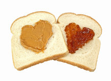 Peanut Butter And Jelly Love. Two slices of bread with hearts of peanut butter and jelly isolated on a white background royalty free stock photography