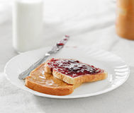 Peanut butter and jelly on pieces of bread. stock photography