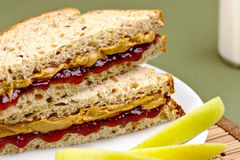 Peanut butter and jelly sandwich. Healthy and delicious childs lunch of peanut butter and jelly sandwich with green apples and milk stock image