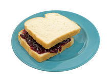 Peanut butter and jelly sandwich. A peanut butter and jelly sandwich on white bread with jelly showing on a blue plate royalty free stock photography