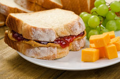 Peanut Butter and Jelly Sandwich. A delicious peanut butter and jelly sandwich with strawberry jam, cheddar cheese, and grapes Royalty Free Stock Photos