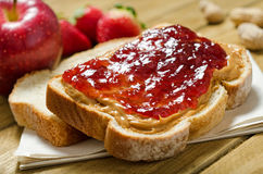 Peanut Butter and Jelly Sandwich. With apple, strawberries, and peanuts in the shell Stock Photo