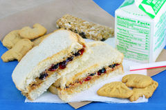 Peanut Butter and Jelly Sandwich Bag Lunch. One peanut butter and jelly sandwich with a granola bar, cookies and carton of milk on a brown lunch bag royalty free stock images