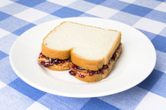 Peanut butter and jelly sandwich. A delicious peanut butter and jelly sandwich with grape jam ready to be eaten during lunchtime royalty free stock photos