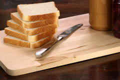 Peanut butter and jelly sandwich ingrdients. Peanut butter and jelly sandwich ingredients on preparation wood board with jars and bread stock photos