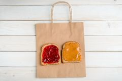 Jam sandwich on paper bag. Peanut butter and jelly sandwich on paper bag, top-view. Light wooden boards background. Popular snack stock photos