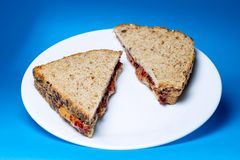 Peanut butter and jelly sandwich on white glass plate stock images