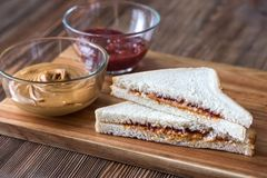 A peanut butter and jelly sandwich. On the wooden board royalty free stock image