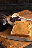 Peanut Butter and Jelly Sandwich on a Wooden Kitchen Counter. Fixing a Peanut Butter and Jelly Sandwich on a Wooden Kitchen Counter stock image