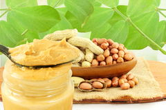 Peanut butter and peanuts whole and peeled in leaves background stock photography