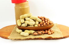 Peanut butter and peanuts whole and peeled Royalty Free Stock Images