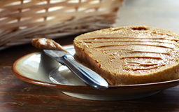 Peanut butter sandwich. Peace of white bread spread with peanut butter with knife on the plate Royalty Free Stock Images