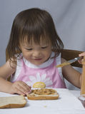 Peanut Butter Sandwich. A young asina girl making a peanut butter and jelly sandwich Stock Image