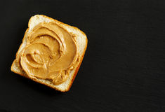 Peanut butter sandwich on black background. Royalty Free Stock Photo