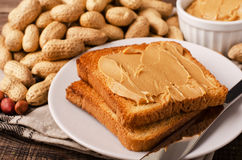 Peanut butter sandwich on plate. With inshell peanuts, breakfast on the wooden background Royalty Free Stock Photo