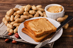 Peanut butter sandwich on plate with inshell peanuts. Breakfast on the wooden background Stock Photos
