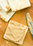 Peanut butter spread on crackers. Stock Photos
