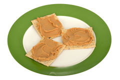 Peanut Butter Spread on Seeded Crackers. On a plate isolated white background Royalty Free Stock Image