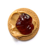 Peanut butter and strawberry jam on biscuit. Creamy peanut butter and strawberry jam spread on round shortbread cookie royalty free stock images