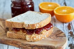 Peanut Butter and Strawberry Jelly Sandwich on Oat Bread. Homemade Peanut Butter and Jelly Sandwich on oat bread, over a rustic wooden background with fruit in stock photo