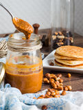 Peanut butter to eat a teaspoon of jars, pancakes Royalty Free Stock Photography